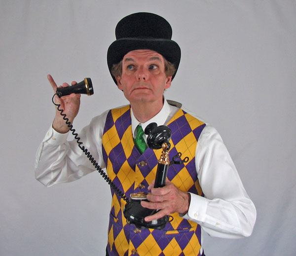 Magician in purple and gold diamond pattern vest wearing top hat and holding old fashioned candlestick telephone.